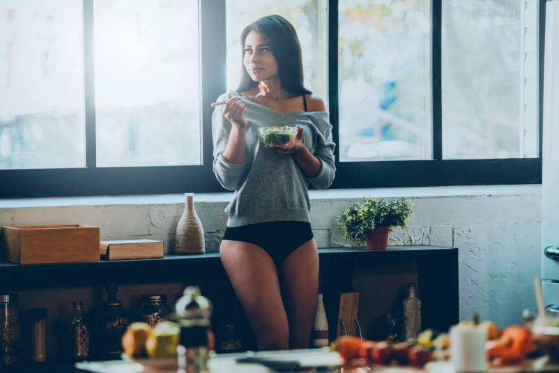 woman in underwear eating salad