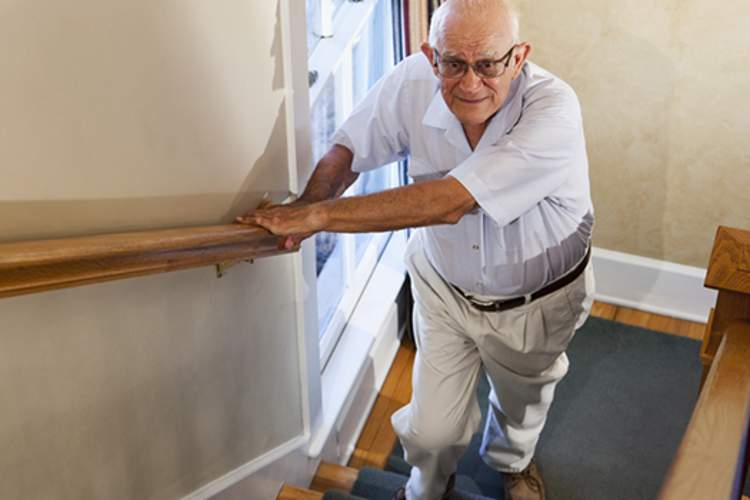 older man with leg pain walking upstairs image