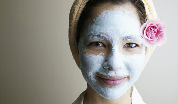 Young woman with facial mask on image.