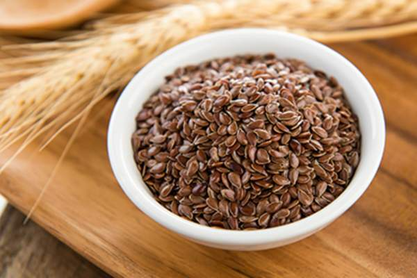 Flaxseeds in white bowl on wood table.