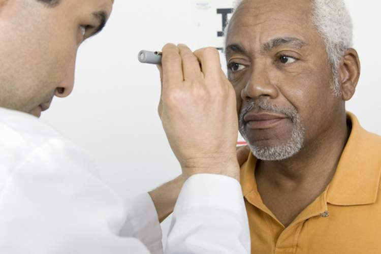 A doctor checks a patient's eyes for diabetic macular edema.