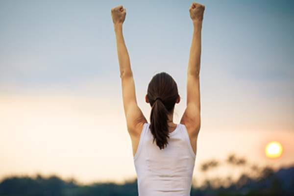 Woman with her hands raised in the air victoriously.