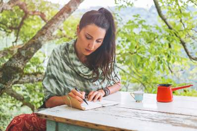 Woman writing a letter in a journal.