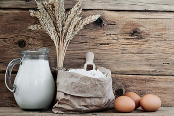 Bag of flour with spikelets of wheat, milk and eggs.