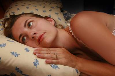 Woman with insomnia lying awake in bed.