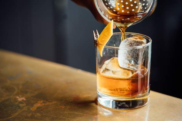 Bartender pouring whisky cocktail
