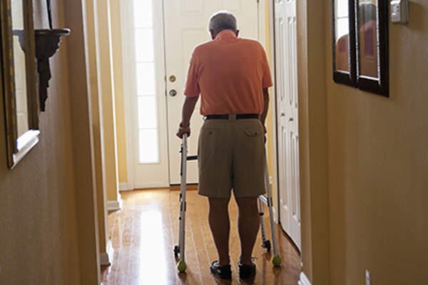 Senior using a walker to get around his home.