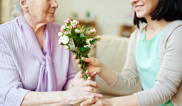 Woman giving her senior mother a bouquet of flowers.