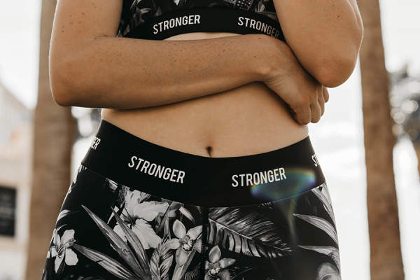 "Woman wearing pants that read ""STRONGER"", stomach visible"