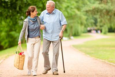 Senior walking with his caregiver.