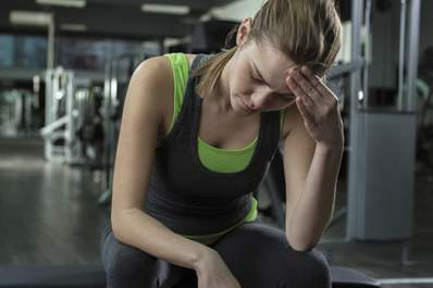 woman with migraine headache at gym image