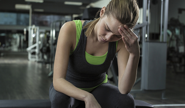woman with migraine at gym image