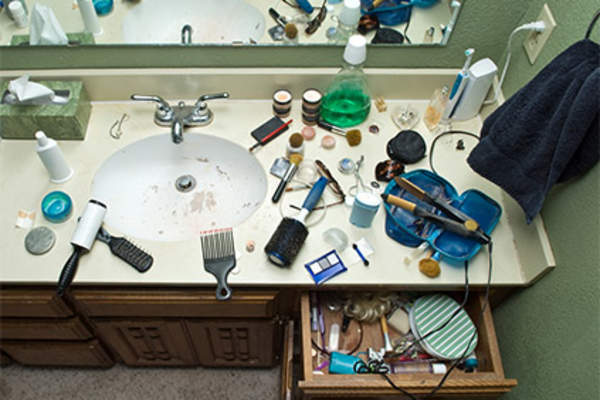 Makeup all over messy bathroom sink.