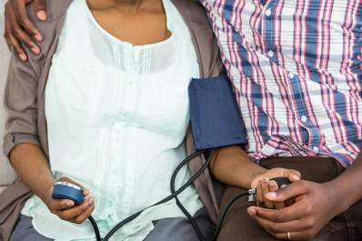 Couple at home, woman taking her blood pressure.