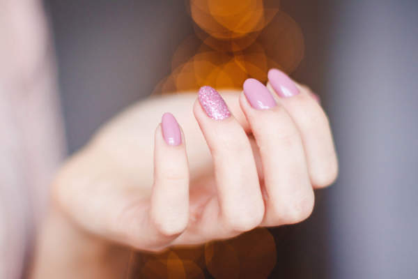 fingers curled with pink manicure