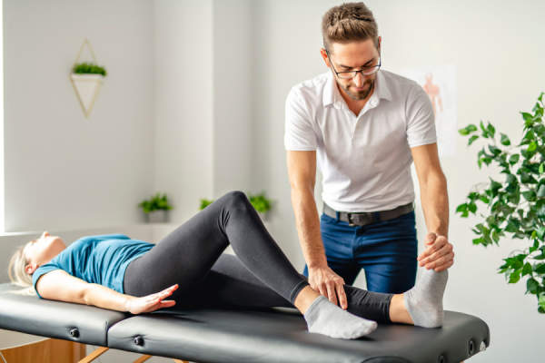 rehabilitation physiotherapy man at work with woman client working on foot