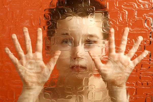 Mindblindness concept child behind frosted glass