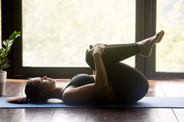 Woman on yoga mat doing knees to chest pose.