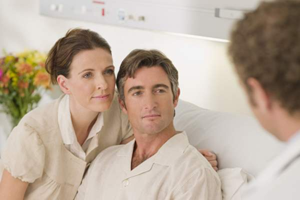 couple talking to doctor in hospital image