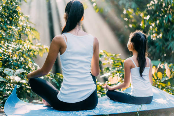 Mother and daughter meditating in lotus position