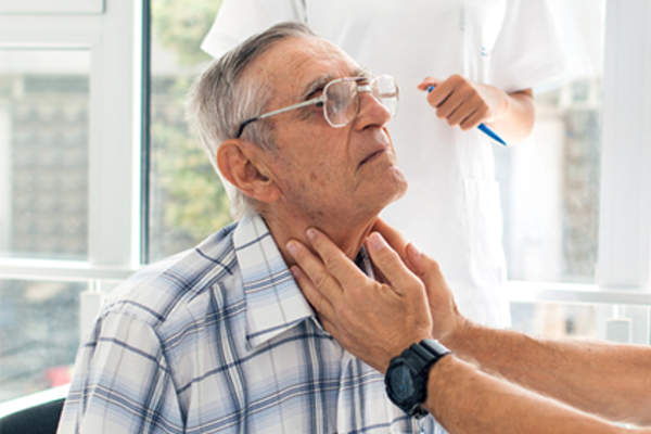 Doctor checking lymph nodes in neck in senior man.