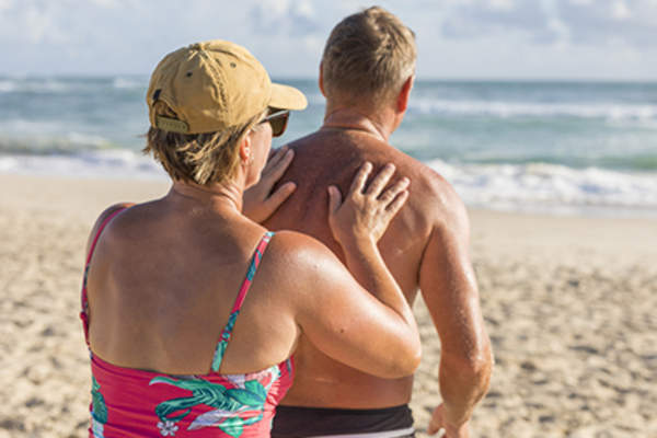 Woman putting sunscreen on man's back at the beach.