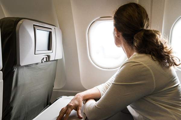 woman looking out plane window image