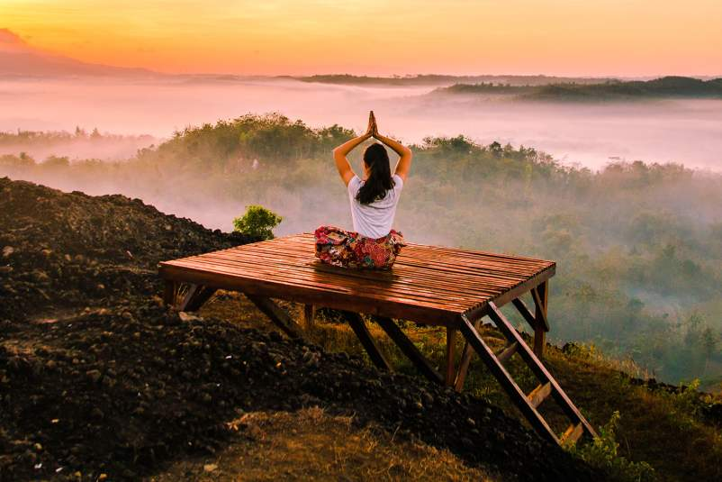 Woman meditating in beautiful landscape.