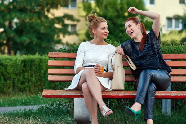 Couple sitting a park bench finding something humorous