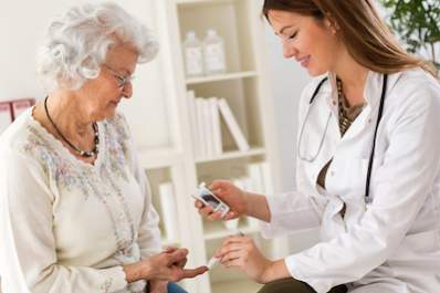 A doctor helps an elderly woman check her blood glucose level.