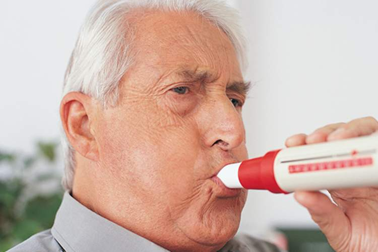 Senior man blowing into a spirometer for a spirometry test.