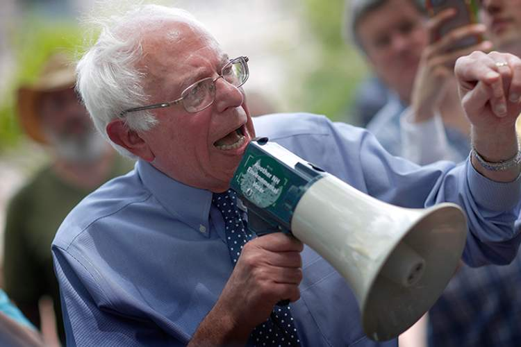 Democratic presidential candidate and U.S. Sen. Bernie Sanders (I-VT) speaks to an overflow crowd through a megaphone after a campaign event at the New England College.