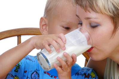 Boy giving his Mom a drink of milk.