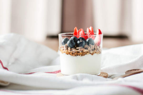 yogurt with fruit and granola on bed