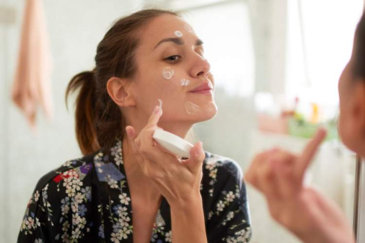 woman putting moisturizing balm on her face