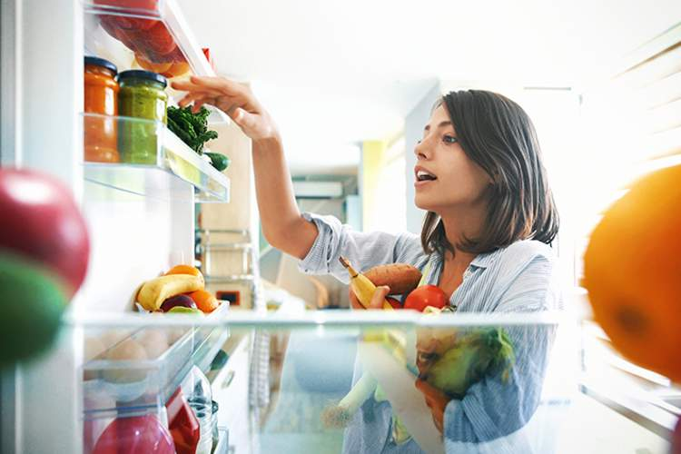 Woman choosing fruits and vegetables from the fridge.