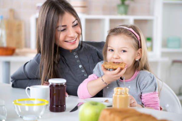 Mother with child eating peanut butter on bread image.