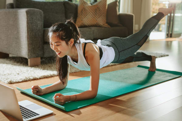 Young woman working out to online program.