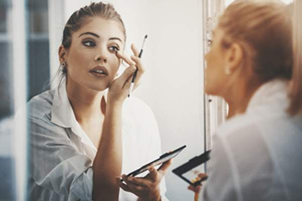 Woman putting on makeup in the mirror.