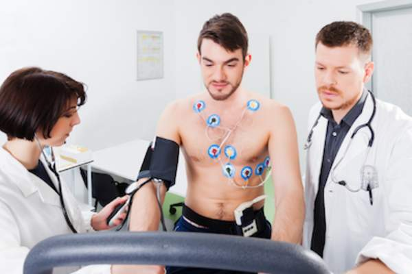Doctors performing exercise stress test on young man.