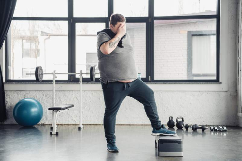 overweight man at the gym, covering face