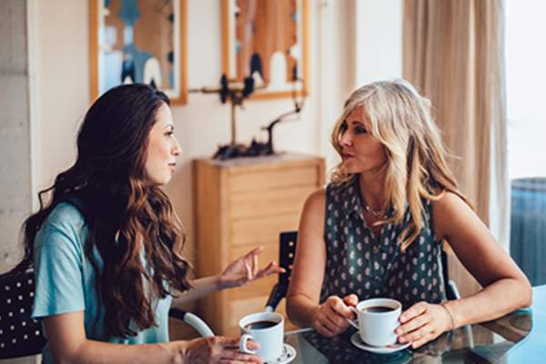 Women talking at a table drinking coffee.