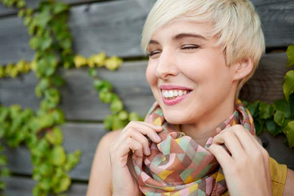Woman wearing silk scarf and smiling.