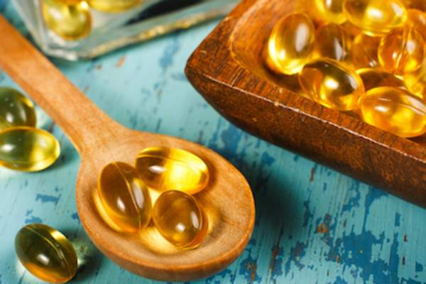 Fish oil pills on wooden spoon and in wooden tray.
