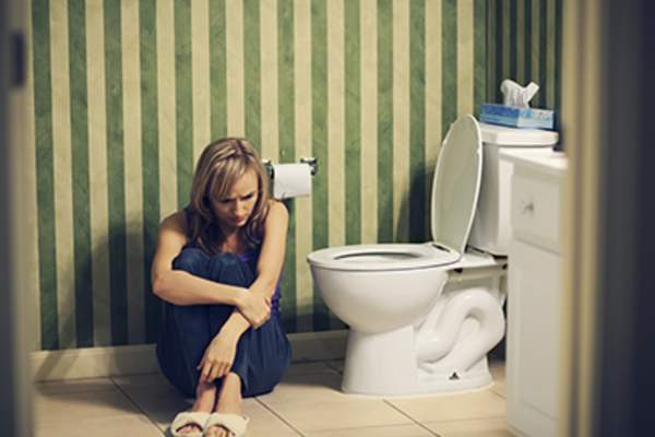 Sad young woman sitting on floor in the bathroom.
