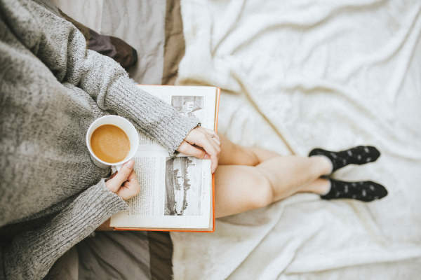 woman in sweater drinking tea and reading book in bed