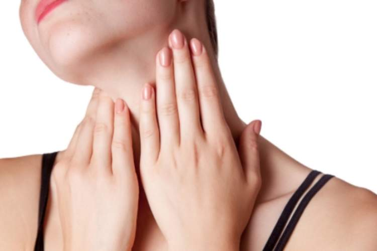 Young woman feeling a lump in her neck.