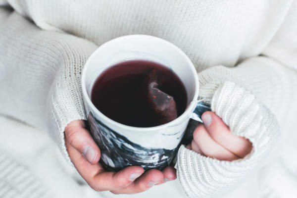 person in sweater holding tea