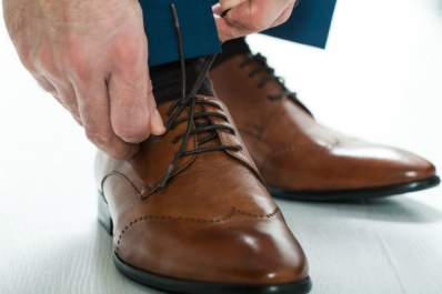 A man puts on shoes with gel insoles for his knee pain.