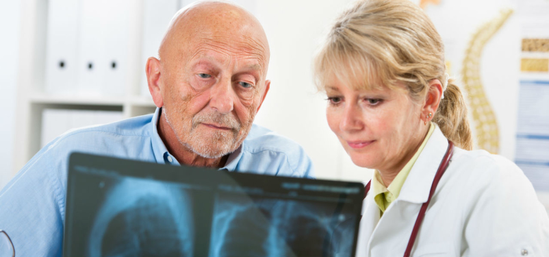 man reviewing lung x-ray with doctor